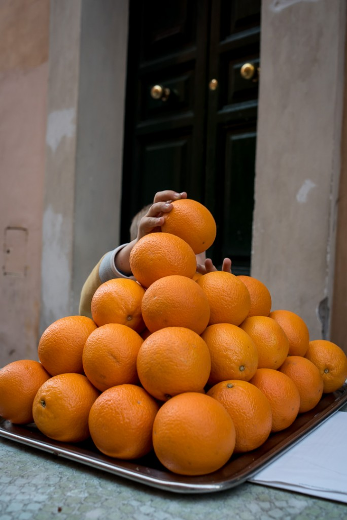 Boy reaching fro oranges-Rome-street photgraphy Tim Fox