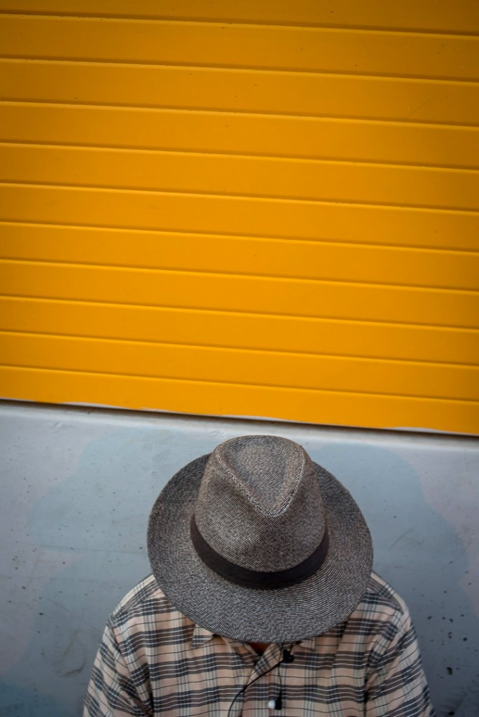 Man in hat against yellow wall -Rome-street photographer Tim Fox