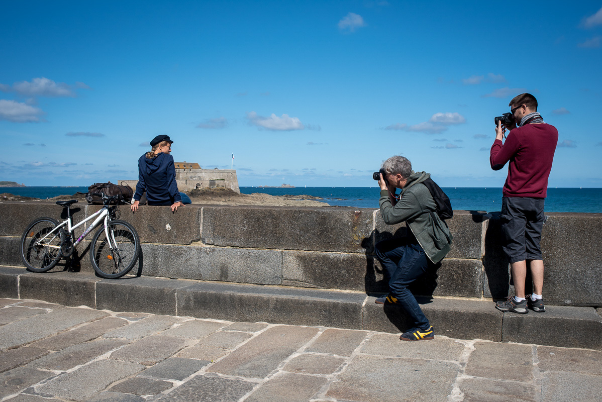 Two photographers photograph a young woman with a hat, sitting on a wall next a bicycle, looking over the sea in Saint Malo